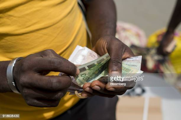 A man counts out West African CFA franc currency banknotes by the fishing harbour in the port area of Bissau GuineaBissau on Saturday Feb 10 2018 The...