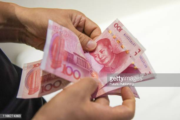 Man counts renminbi banknotes in Haikou in south China's Hainan province Friday, Sept. 06, 2019. China will cut the reserve requirement ratio for...