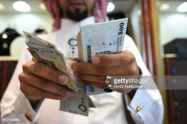 A man counts Saudi riyal banknotes at his jewelry shop in Tiba market in the capital Riyadh on October 3 2016 / AFP / FAYEZ NURELDINE