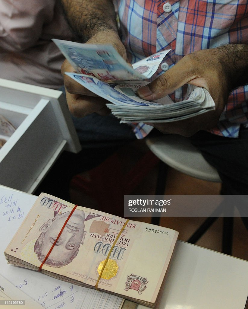 A man counts Singapore notes at a money changer in Singapore on ...