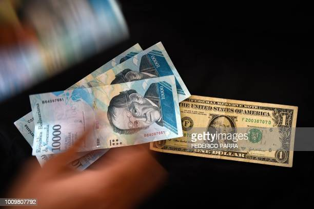 Man counts Venezuelan bolivar banknotes next to a US one-dollar bill in Caracas on August 2, 2018. - Venezuela's government on Thursday loosened the...