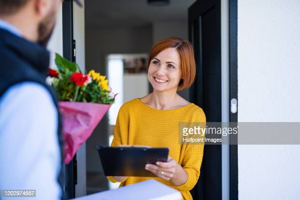 man courier delivering bouquet of flowers to a young woman, midsection. - receiving stock pictures, royalty-free photos & images