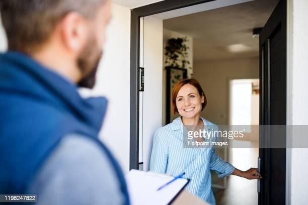man courier delivering parcel to a young woman. - deurkozijn stockfoto's en -beelden