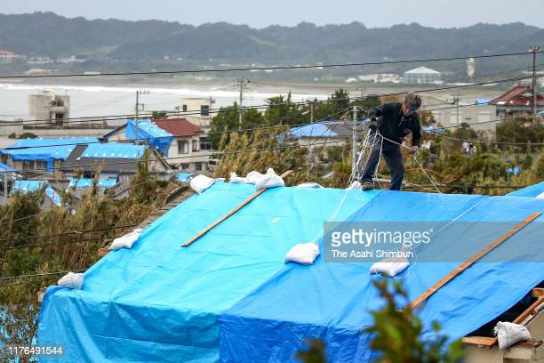 A man cover the damaged roof with tarp 10 days after Typhoon Fahsai hit the region on September 22 2019 in Tateyama Chiba Japan