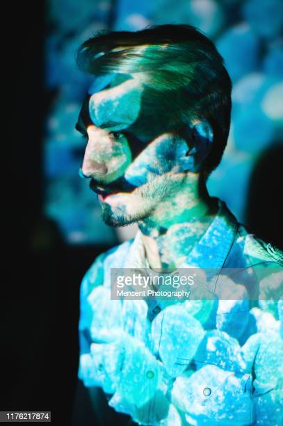 man covered by colorful abstract patterns projected onto his face - art and craft product stock pictures, royalty-free photos & images