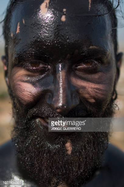 Man covered in black grease poses during the traditional festival of the 'Cascamorras', in Baza, near Granada, on September 6, 2018. - Every year on...