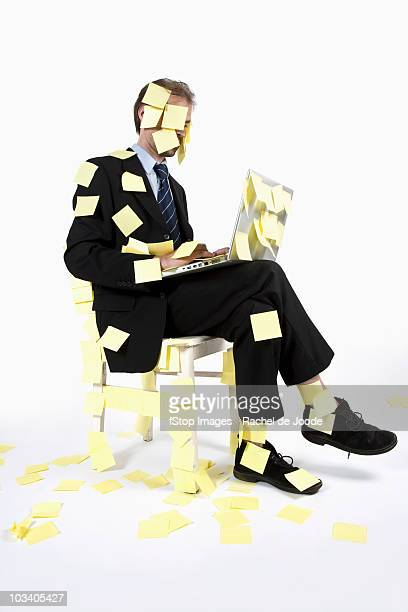 A man covered in blank adhesive notes while sitting and using a laptop
