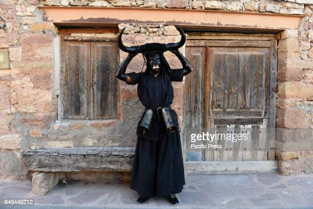 A man covered in oil and soot carrying bull horns on his head and cowbells on a belt representing the devil pictured during a traditional carnival...