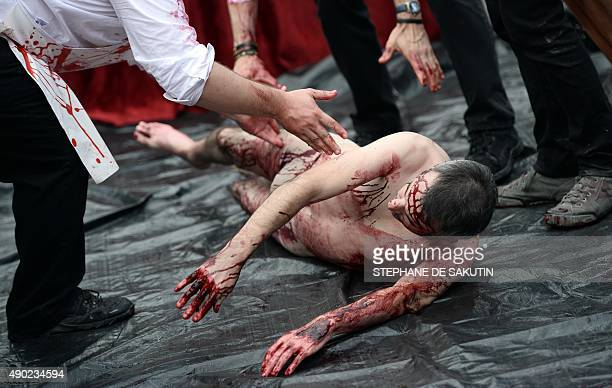A man covered in red paint to represent blood is dragged by his feet as activists of the animal liberation movement 269life stage an open air...