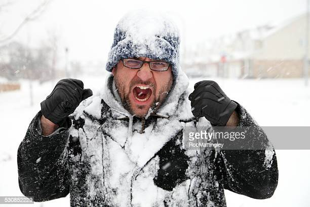 Man Covered In Snow Shakes Fists at Winter