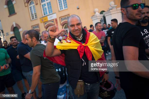 A man covered with a Spanish flag makes a sign as he takes part in a protest in support of national police officers and civil guards attacked by pro...