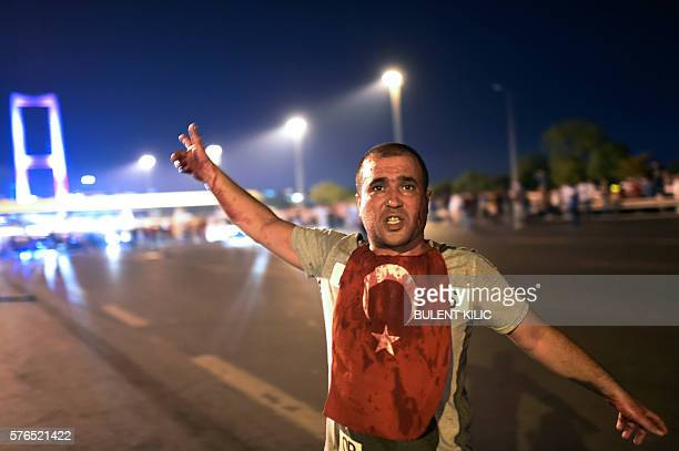 A man covered with blood points at the Bosphorus bridge as Turkish military clashes with people at the entrance to the bridge in Istanbul on July 16...