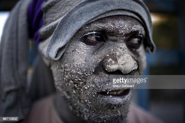 A man covered with debris stands in a neighborhood of Canape Vert on January 16 2010 in PortauPrince Haiti
