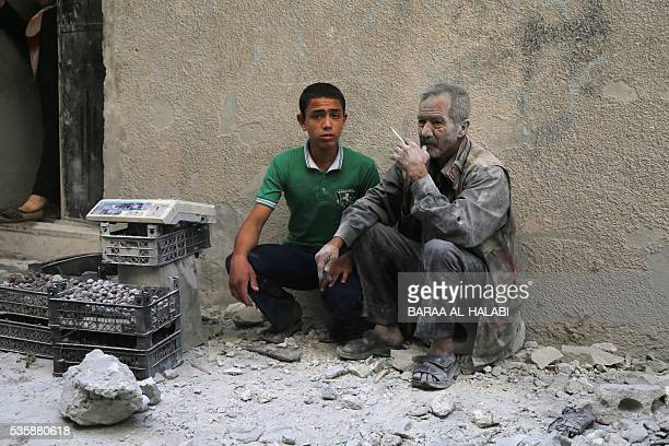 TOPSHOT A man covered with dust sits on a street following a reported air strike by Syrian government forces in the rebelheld neighbourhood of...