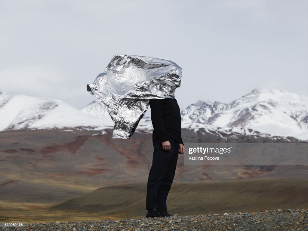 Man covered with silver foil against the mountains