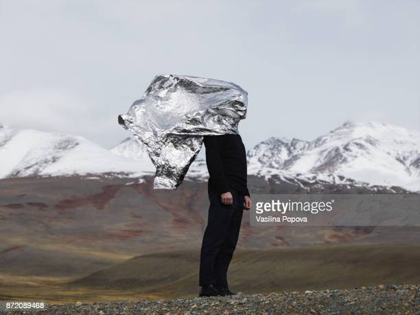 Man covered with foil against nature background