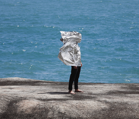 Man covered with foil against sea background - gettyimageskorea