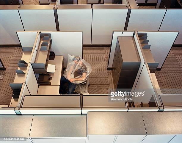 man covered with plastic wrap in cubicle, elevated view - man wrapped in plastic stock pictures, royalty-free photos & images