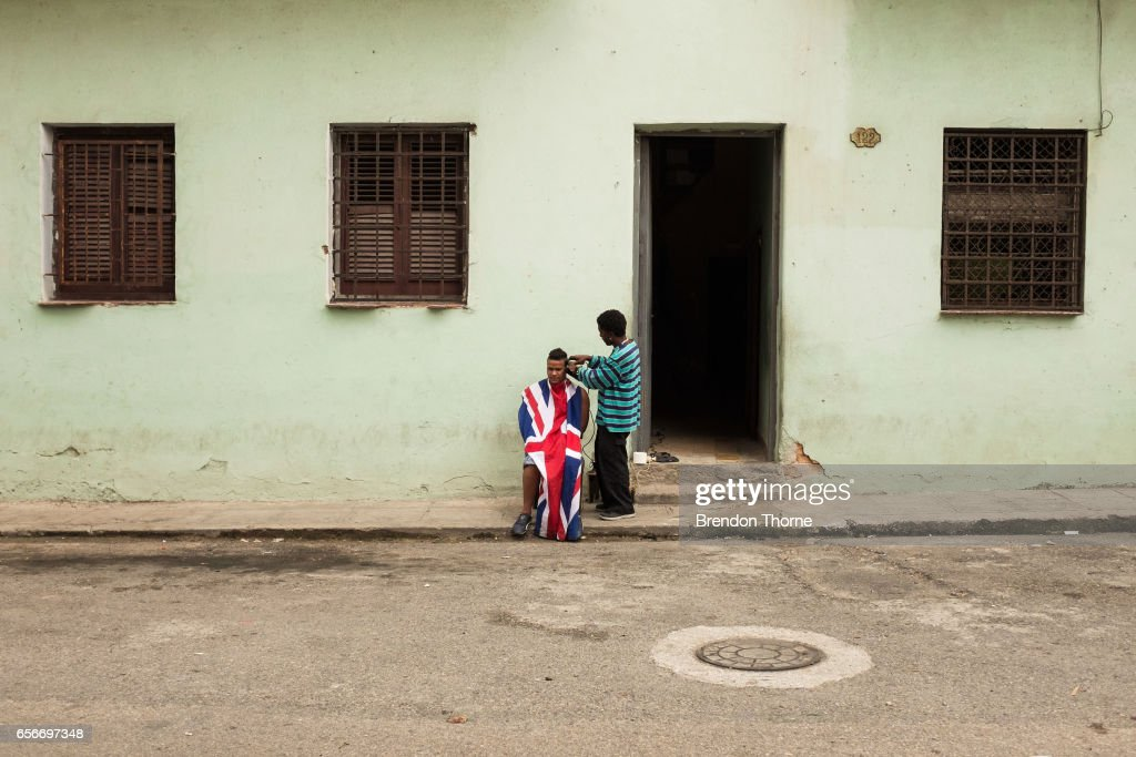 A man covered with The Union Jack flag receives a haircut in Central Havana on January 29, 2017 in Havana, Cuba.