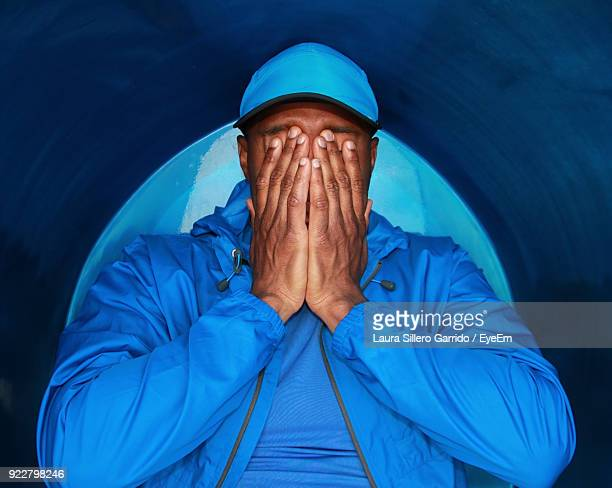 man covering face against blue wall - laura cover stock pictures, royalty-free photos & images