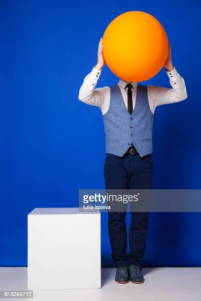 Man covering face with ball