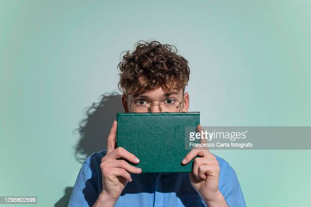 man covering face with book - book stock pictures, royalty-free photos & images