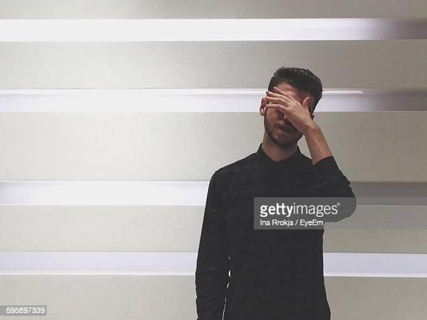 man covering face with hand - obscured face stock photos and pictures