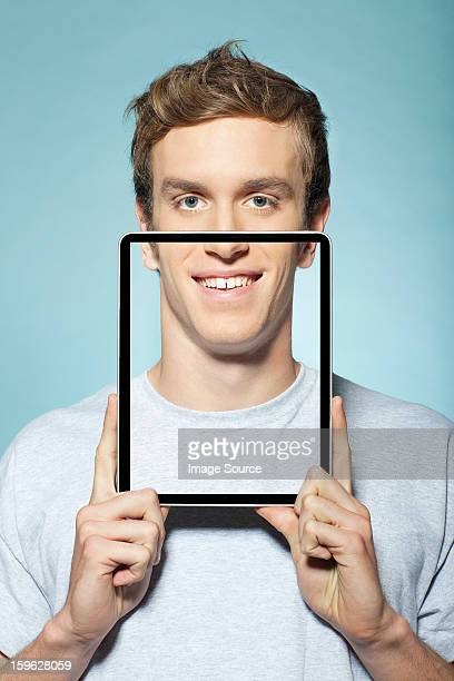 Man covering half his face with digital tablet