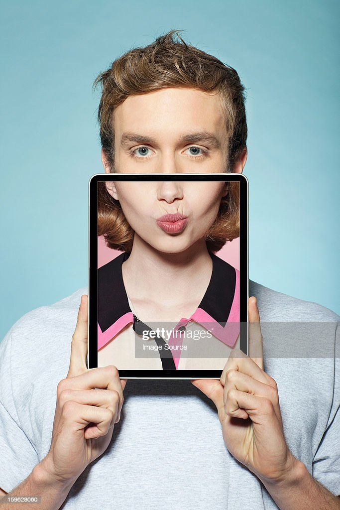 Man covering half his face with digital tablet, with womans mouth : Stock Photo