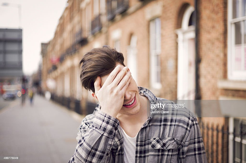 man covering his eyes in a laugh on the street : Stock Photo