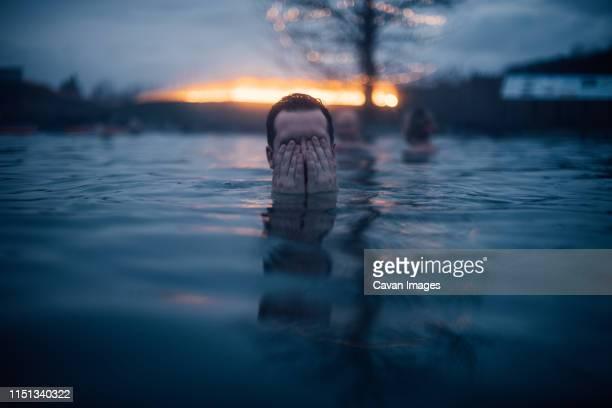man covering his eyes in the water at the secret lagoon in iceland - lagune stockfoto's en -beelden