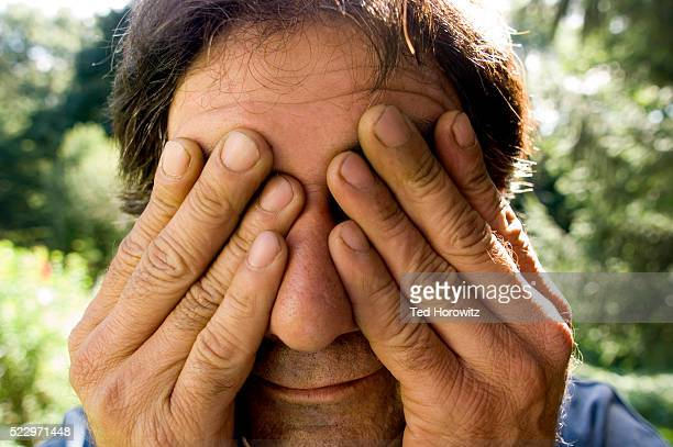 Man covering his eyes