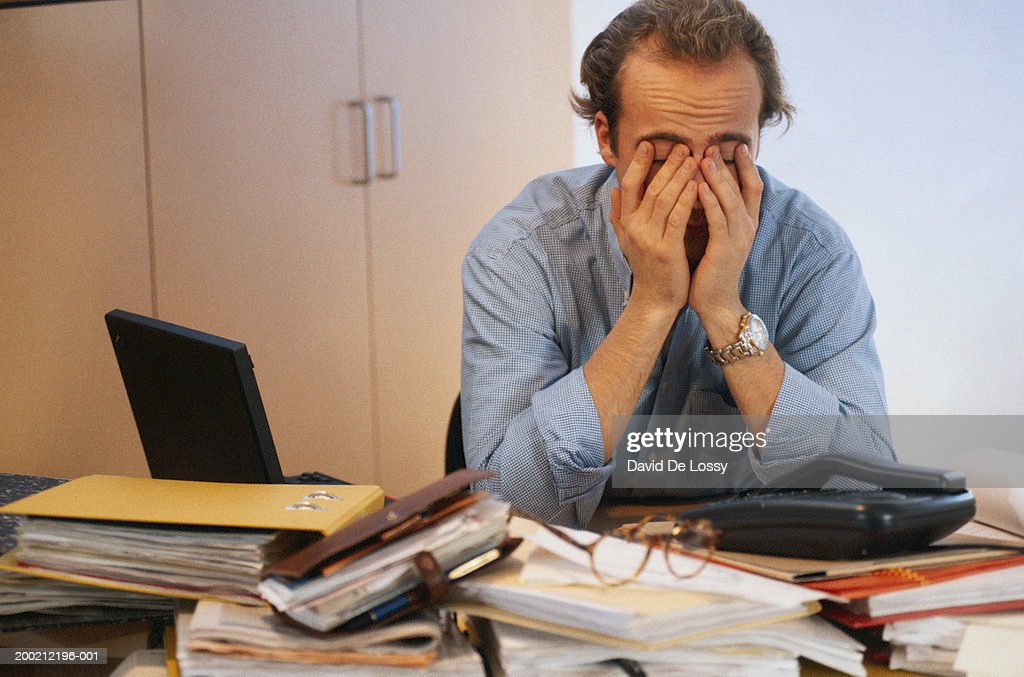 Man covering his face in office : Stock Photo