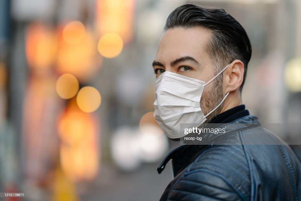 Man covering his face with pollution mask for protection from viruses : Stock Photo