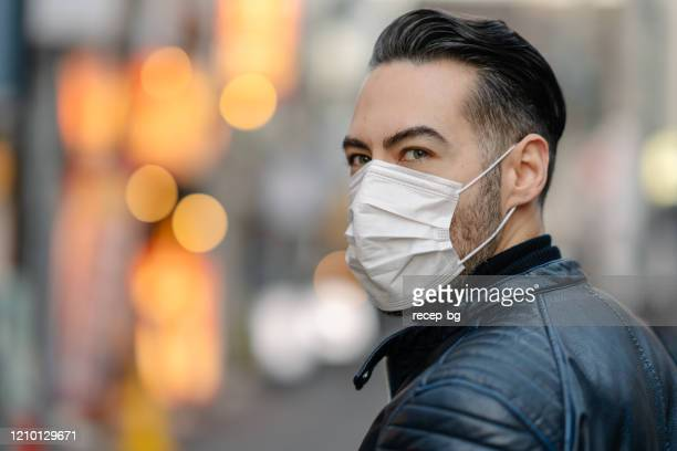 homme couvrant son visage avec le masque de pollution pour la protection contre des virus - masque de chirurgien photos et images de collection