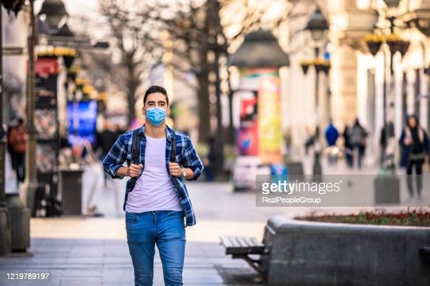 mens die zijn gezicht met verontreinigingsmasker voor bescherming tegen virussen behandelt - real people stockfoto's en -beelden