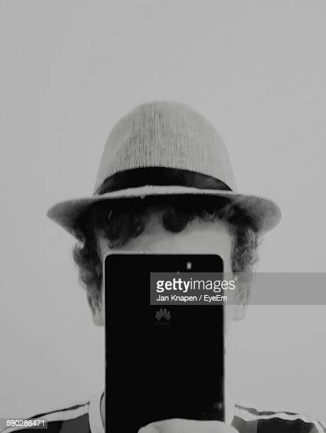 Man Covering His Face With Smart Phone Against White Background