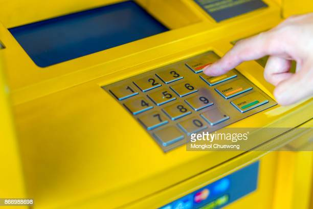 Man covering his hands whilst entering his PIN at an ATM