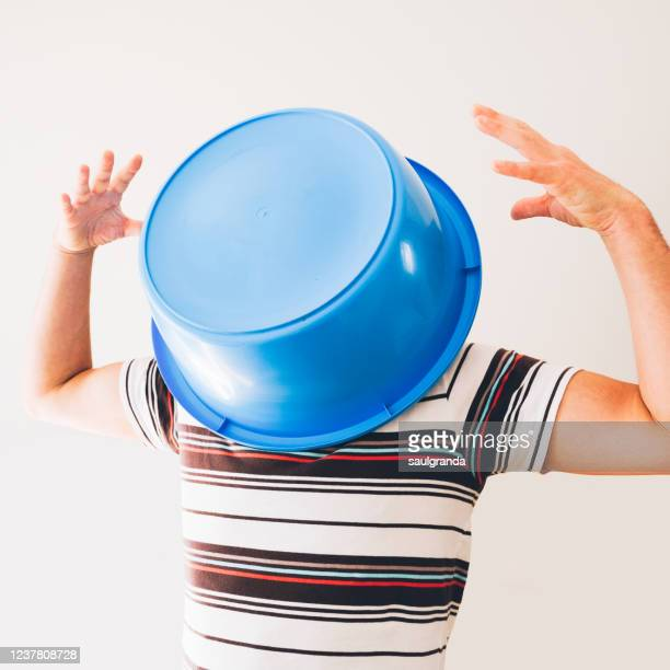 man covering his head with a plastic bucket - wash bowl stock pictures, royalty-free photos & images