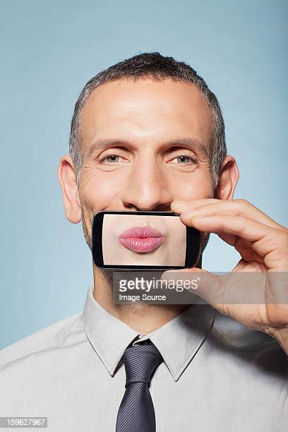 Man covering mouth with smartphone