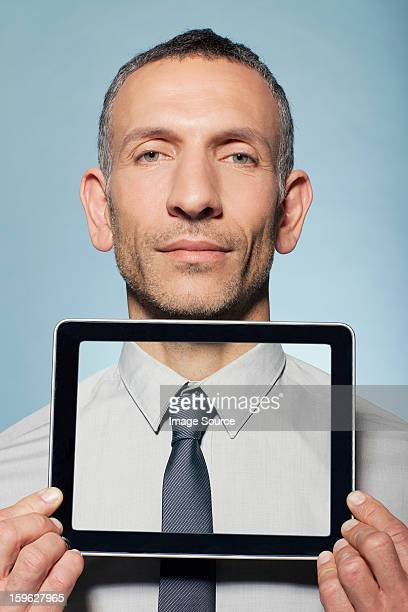 Man covering neck with digital tablet