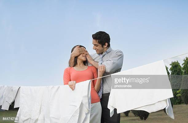 Man covering woman's eyes and smiling