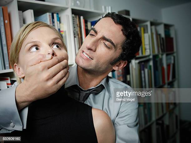 Man Covering Woman's Mouth