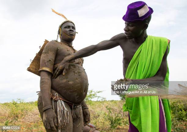 A man covers a Bodi tribe fat man with cow dungs during Kael ceremony Omo valley Hana Mursi Ethiopia on June 2 2017 in Hana Mursi Ethiopia