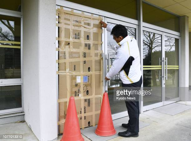 A man covers a broken glass door at an elementary school in the town of Nagomi Kumamoto Prefecture on Jan 4 after an earthquake with an estimated...