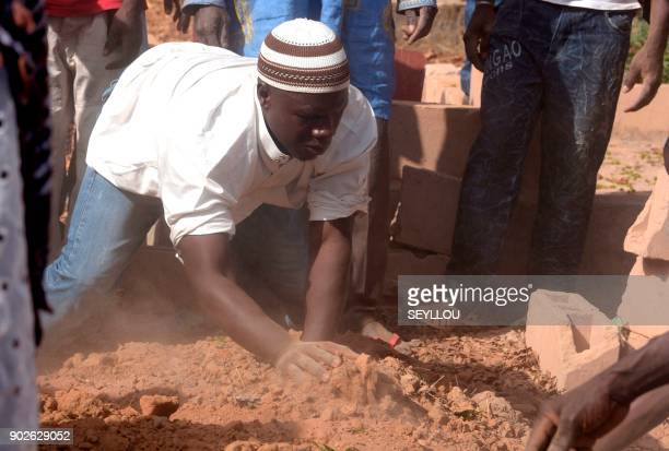 A man covers a grave with sand during a burial in a cemetery in the regional capital Ziguinchor southern Senegal on January 7 2018 following an...