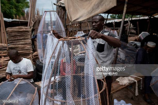 A man covers a wooden frame with fishing net to construct a fish trap in Baga fish market in in Maiduguri on July 31 2017 The fish trade in Borno...