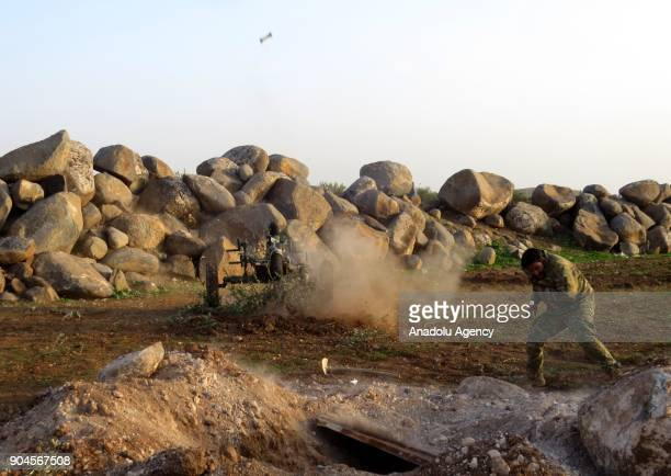 A man covers himself as a mortar is launched within the clashes between armed opposition group Tahrir alSham and Assad Regime forces around the Abu...