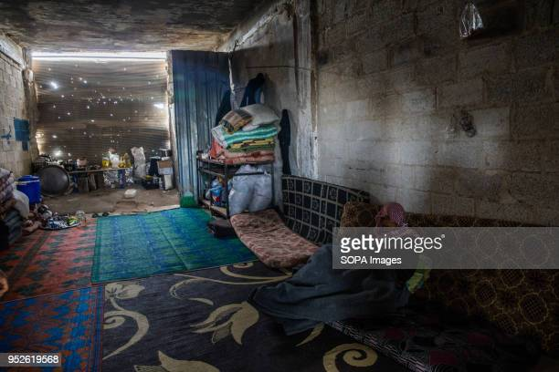 A man covers himself for warmth in the back of an empty shop now housing his family after displacement from Afrin An estimated 400000 refugees...
