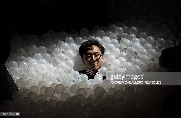 A man covers himself in plastic balls at 'The Beach' art installation at the National Building museum in Washington DC on September 6 2015 The Beach...